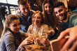 canvas print picture - Group of young friends having fun in restaurant talking, laughing while dining at table and making selfie.