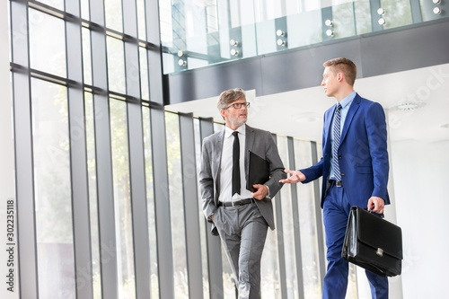 Obraz Businessmen discussing plans before meeting in office - fototapety do salonu