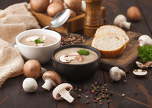 Ceramic Bowl Plates Of Creamy Chestnut Champignon Mushroom Soup With Spoon, Pepper And Kitchen Cloth On Dark Wooden  Background And Box Of Raw Mushrooms.