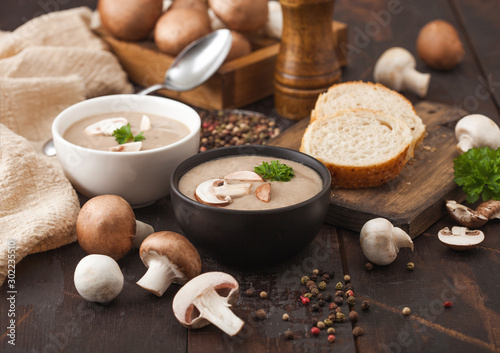 Ceramic bowl plates of creamy chestnut champignon mushroom soup with spoon, pepper and kitchen cloth on dark wooden  background and box of raw mushrooms Wallpaper Mural