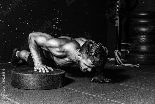 Fotografija  Young strong sweaty focused fit muscular man with big muscles performing push up