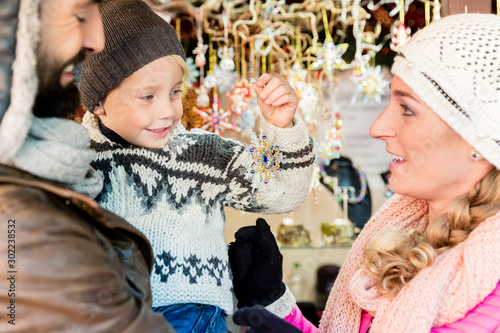 Family on Christmas market buying ornaments and baubles