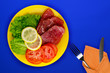canvas print picture - ham with lettuce, tomatoes and lemon on a yellow plate. ham on a blue background. smoked food top