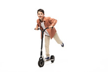 Excited Boy Riding Kick Scooter While Looking At Camera On White Background