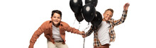 Panoramic Shot Of Two Happy Boys With Black Festive Balloons Isolated On White