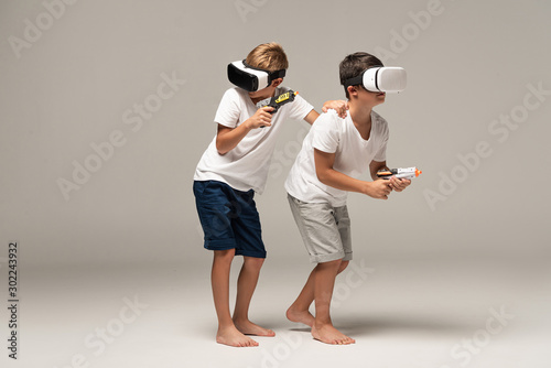 two barefoot brothers in pajamas holding toy guns while using vr headsets on gre Canvas Print