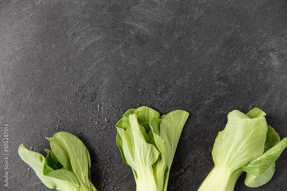 Fototapeta vegetable, food and culinary concept - close up of bok choy chinese cabbage on slate stone background