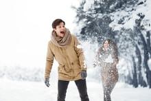 Girlfriend Throwing Snow At Boyfriend Walking In Forest