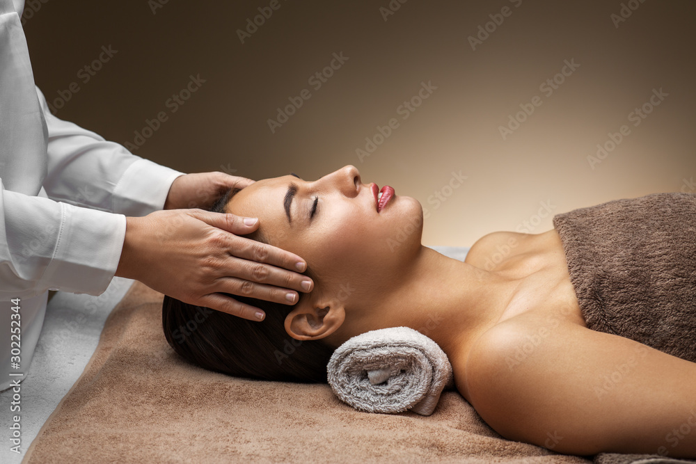 Fototapeta wellness, beauty and relaxation concept - beautiful young woman lying with closed eyes and having face and head massage at spa