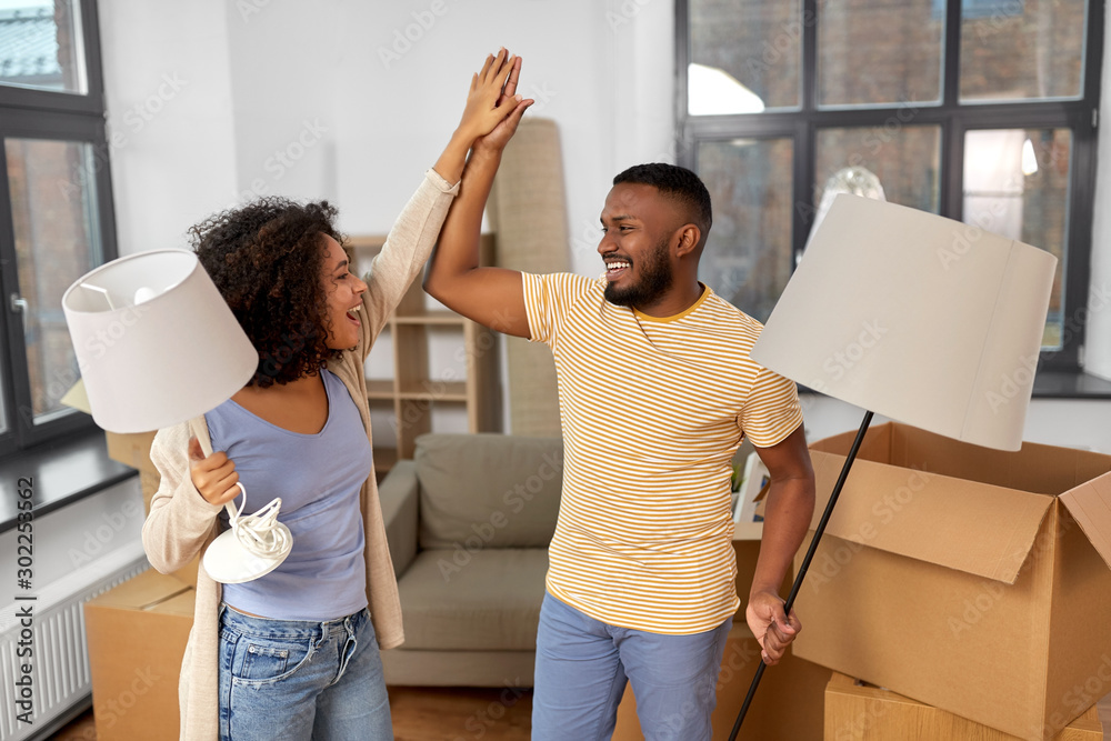 Fototapeta moving, people, repair and real estate concept - happy african american couple with lamps packing stuff into cardboard boxes at home and making high five
