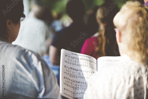 Vászonkép Selective focus shot from behind of people reading notes in the choir with a blu