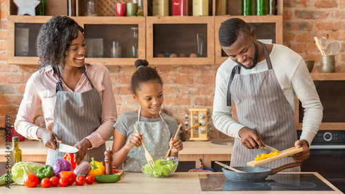Fotografiet Mom and daughter watching dad while cooking together