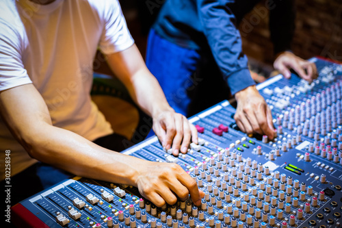 sound engineer and producer mixing sound on audio mixing console in recording, broadcasting studio - 302258348