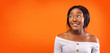canvas print picture - Afro Girl Biting Lips Standing Over Orange Studio Background, Panorama