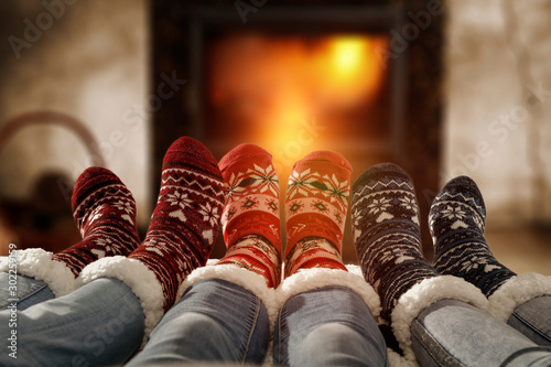 Fototapeta Woman legs in home interior with fireplace.Woolen socks and jeans.Free space for your decoration.Christmas cold winter night.Copy space.  obraz