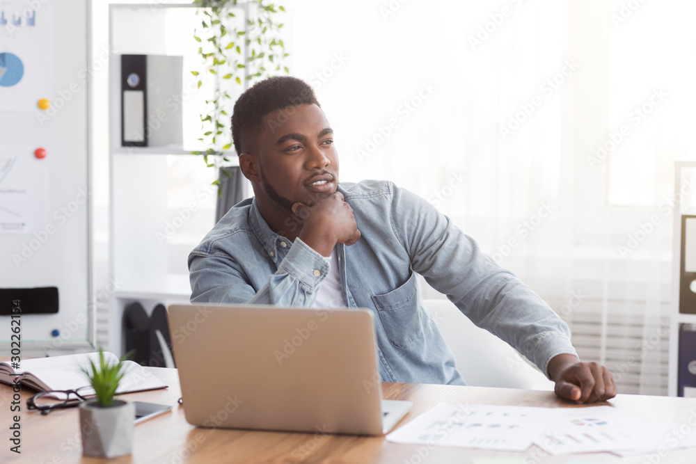 Fototapeta Thoughtful african american employee sitting at workplace in modern office