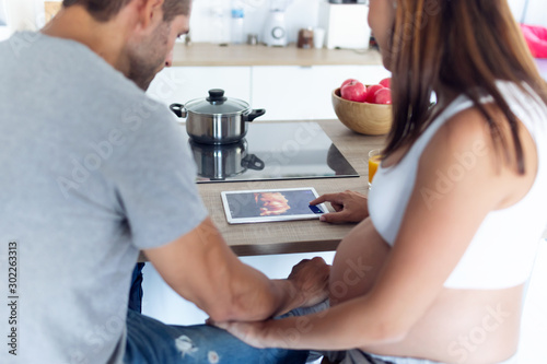Obraz Pretty young pregnant couple looking at their baby's ultrasound on the digital tablet in the kitchen at home. - fototapety do salonu