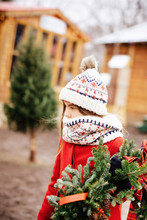 Young Girl Carrying A Christma...
