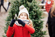 Young Girl At The Christmas Market Holding A Metal Tree Ornament, Outdoors.