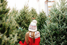 Young Girl Walking In Christmas Tree Lot At The Market