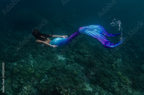 Photo Young female free diver swims underwater in a colorful and sexy mermaid costume