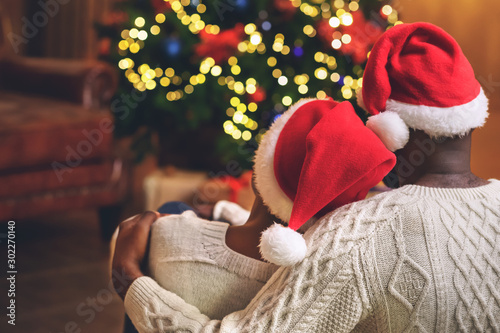 Fotografiet  Couple in santa hats cuddling and looking at Xmas tree