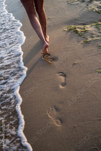 Photo Barefooted female legs, walking along the strip of the sea