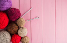 Balls Of Yarn In Different Colors With Knitting Needles On A Background Of Pink Wood Texture