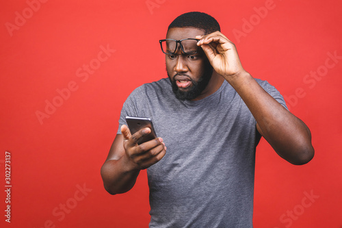 Young african american man using smartphone stressed, shocked with shame and surprise face, angry and frustrated Canvas Print