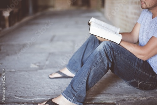 Closeup shot of a male sitting on the ground while reading the bible with a blur Wallpaper Mural