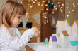 canvas print picture - Little girl opening paper house from Christmas advent calendar in the kids room