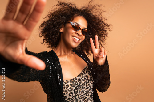 Fotografiet  Spectacular young woman in sunglasses making selfie on beige background