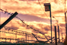 Prison Barbed Wire Fence Enclosing The Prison On The Background Of Storm Clouds And Scarlet Crimson Red Bloody Sunset With A View Of The Birdhouse
