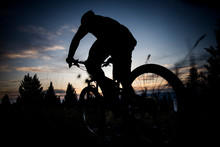 A Mountain Biker Silhouetted A...