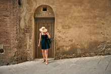 Female In Black Dress Standing By Door