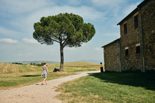 Woman Approaching To Bricked House In Field With Lush Tree