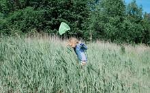 Young Girl Walking Through Long Grass With A Fishing Net In Summer