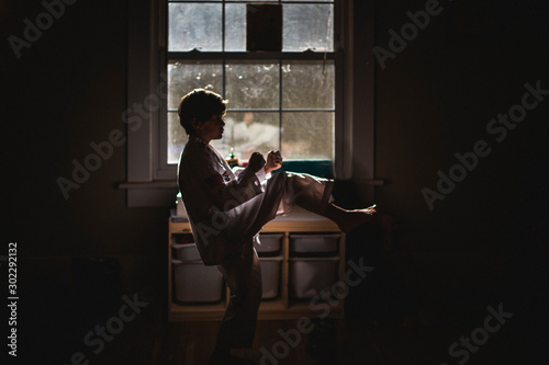 A small boy in uniform practices Taekwondo in early morning light Wallpaper Mural