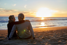 Rear View Of Senior Couple Talking While Sitting On Sand At Beach During Sunset
