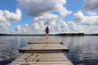 Girl running on a dock at Lake Ranuanjarvi in Finland