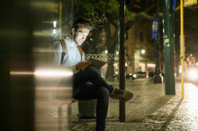 Portrait Of Young Man Waiting At Bus Stop By Night Using Digital Tablet And Earphones, Lisbon, Portugal
