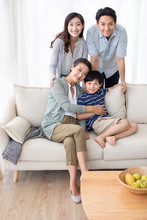 Happy Chinese Family Relaxing On Sofa