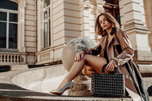 Outdoor Full-length Portrait Of Young Elegant Woman Wearing Beige Trench Coat, Heels, Posing With Classic Black Tweed Bag, Handbag. Copy, Empty Space For Text. Autumn Fashion Advertising Concept.