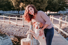 Young Woman And Her Dog Outdoors Walking By A Wood Bridge In A Park With A Lake. Sunny Day, Autumn Season