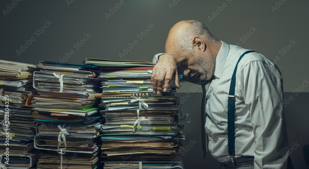 Fototapeta Stressed business executive overloaded with paperwork