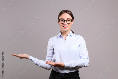 Young beautiful confident businesswoman wearing blue blouse & black frame glasses, standing w/ folded hands & smiling Canvas Print