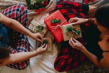 High Angle View Of Two Friends Opening Gifts In Cozy Bed Near Christmas Tree. Closeup Legs Of Women At Home.