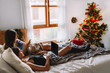 Two women friends in winter holidays at home looking something on laptop near christmas tree in cozy interior. Interior with christmas decorations.