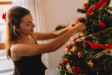 Happy Young Woman Decorating C...