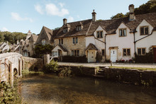 Picturesque View Of Medieval Village Castle Combe With White And Gray Stone Buildings By River In Dorset On Sunny Day